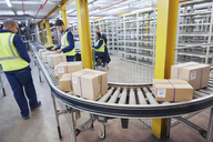 Workers processing cardboard boxes on conveyor belt in distribution warehouse - HOXF02456