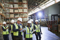 Manager and workers talking in distribution warehouse - HOXF02465
