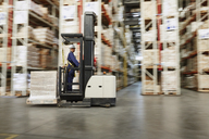 Worker operating forklift moving pallet of boxes in distribution warehouse - HOXF02468