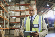 Manager using digital tablet in distribution warehouse - HOXF02471