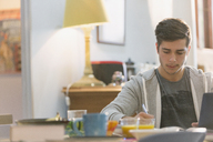 Young man college student studying at breakfast table - HOXF02486