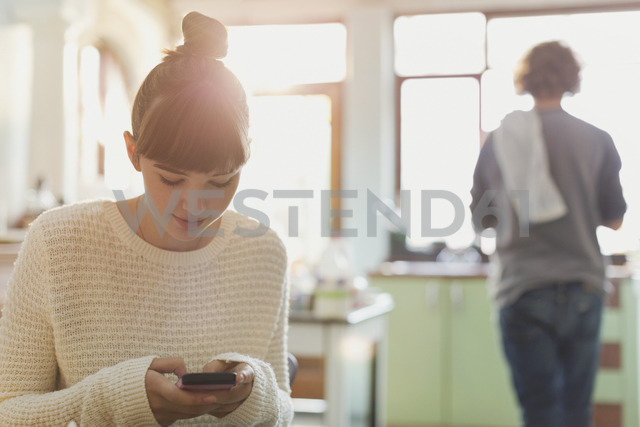 Young woman texting with cell phone in kitchen - HOXF02501 - Justin Pumfrey/Westend61