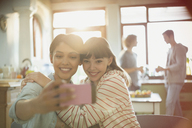 Young women friends roommates hugging taking selfie with camera phone - HOXF02543