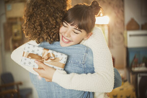 Enthusiastic young woman hugging boyfriend holding birthday gift - HOXF02561