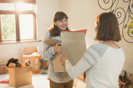 Mother helping young adult daughter moving into new apartment - HOXF02585