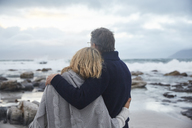 Serene couple hugging on winter beach - HOXF02594