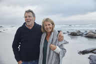Portrait smiling senior couple hugging on stormy beach - HOXF02597