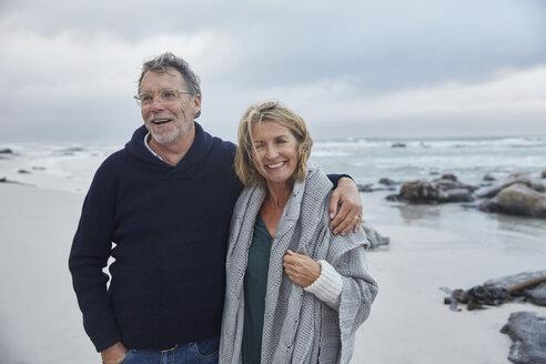 Portrait smiling senior couple hugging on stormy beach - HOXF02597
