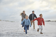 Playful family running on winter beach - HOXF02603