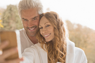 Affectionate couple smiling taking selfie with camera phone outdoors - HOXF02687