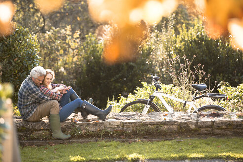 Affectionate couple hugging on stone wall in autumn park - HOXF02693