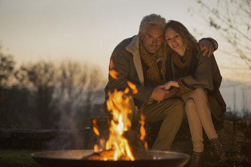 Affectionate serene couple enjoying autumn campfire - HOXF02699