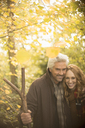 Portrait smiling couple with walking stick in autumn woods - HOXF02711
