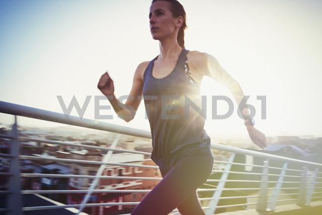 Determined female runner running on urban footbridge - HOXF02714 - Ryan Lees/Westend61