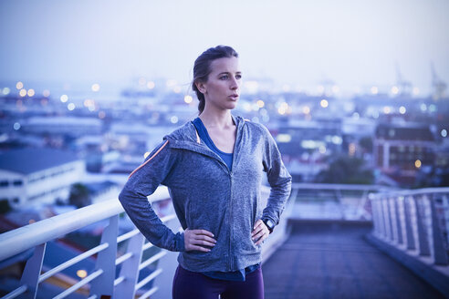 Determined female runner resting on urban footbridge at dawn - HOXF02717