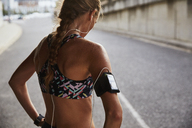 Fit female runner in sports bra with mp3 player armband and headphones resting on urban street - HOXF02720
