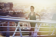 Determined female runner running up urban footbridge at sunrise - HOXF02723