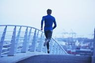 Male runner running on urban footbridge at dawn - HOXF02726