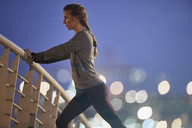 Determined female runner stretching legs on footbridge at dawn - HOXF02735