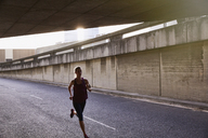 Female runner running into urban tunnel - HOXF02747