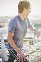 Sweaty male runner resting stretching legs on sunny urban footbridge - HOXF02759