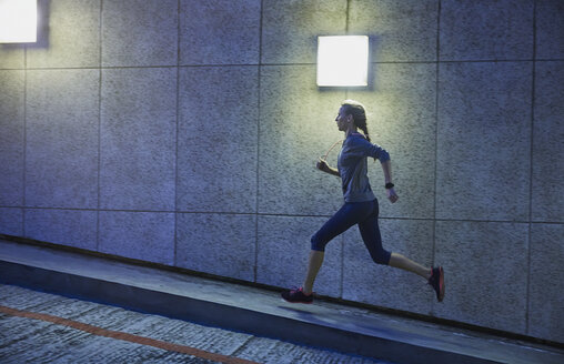 Female runner running ascending illuminated urban ramp - HOXF02762