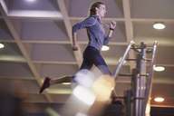 Female runner running above stairs - HOXF02765