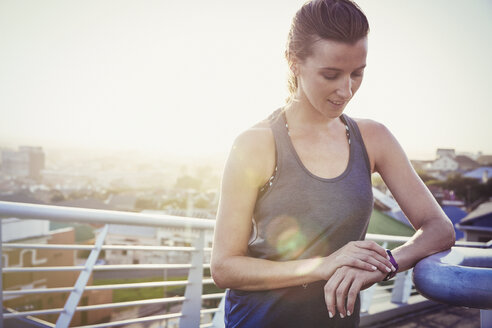 Female runner resting checking smart watch fitness tracker on sunny urban footbridge - HOXF02768