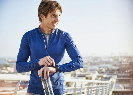 Smiling male runner resting checking smart watch fitness tracker on sunny urban footbridge - HOXF02774