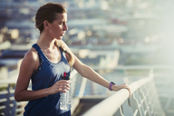 Female runner with water bottle resting on sunny urban footbridge - HOXF02780
