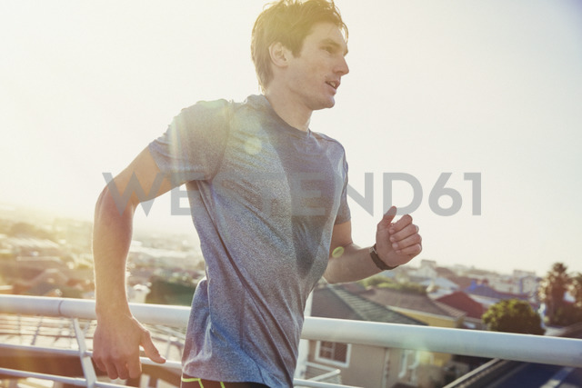 Sweaty male runner running on sunny urban footbridge at sunrise - HOXF02783