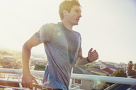 Sweaty male runner running on sunny urban footbridge at sunrise - HOXF02783