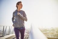 Female runner running on sunny urban footbridge at sunrise - HOXF02789