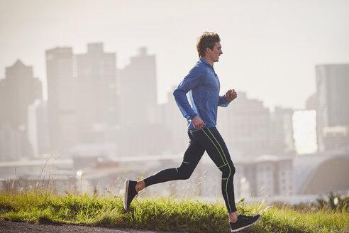 Male runner running on sunny urban street - HOXF02792