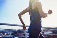 Female runner running on sunny urban footbridge - HOXF02795