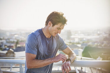 Sweaty male runner resting checking smart watch fitness tracker at sunny urban railing - HOXF02801