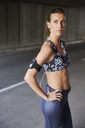 Serious fit female runner in sports bra with mp3 player armband and headphones on urban street - HOXF02804