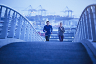 Runner couple running on urban footbridge at dawn - HOXF02810
