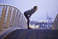 Female runner resting on urban footbridge at dawn - HOXF02816