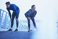 Runner couple stretching legs on footbridge - HOXF02822