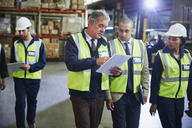 Manger and workers with clipboard talking in distribution warehouse - HOXF02831