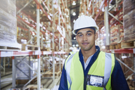 Portrait confident worker in hard-hat in distribution warehouse aisle - HOXF02837