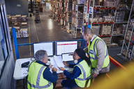 Managers at laptop and computers discussing paperwork in distribution warehouse - HOXF02843