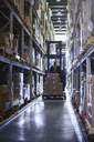 Worker driving forklift with cardboard boxes in aisle of distribution warehouse - HOXF02858