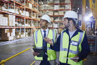 Manger and worker with clipboard and digital tablet talking in distribution warehouse - HOXF02870