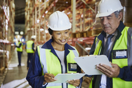 Manager and worker with clipboards meeting in distribution warehouse - HOXF02879