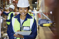 Portrait smiling female worker with clipboard in distribution warehouse - HOXF02891