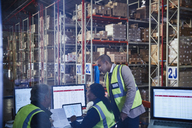 Managers meeting working at laptop and computers in distribution warehouse - HOXF02900