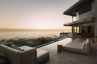 Tranquil sunset ocean view beyond modern luxury home showcase patio - HOXF02912