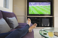 Personal perspective woman with bare feet up watching soccer game on TV in living room - HOXF02915